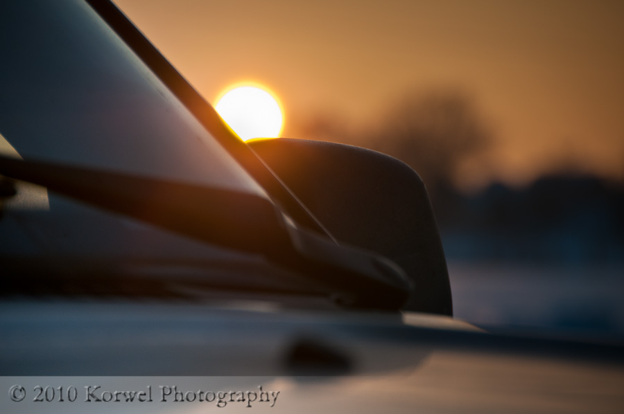 Sunset bokeh on the side mirror of a car